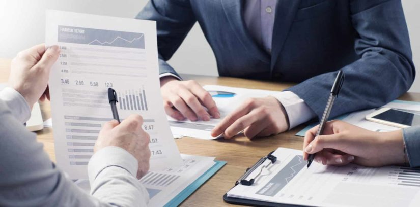 Financial service professional team at work, hands close with business reports and paperwork
